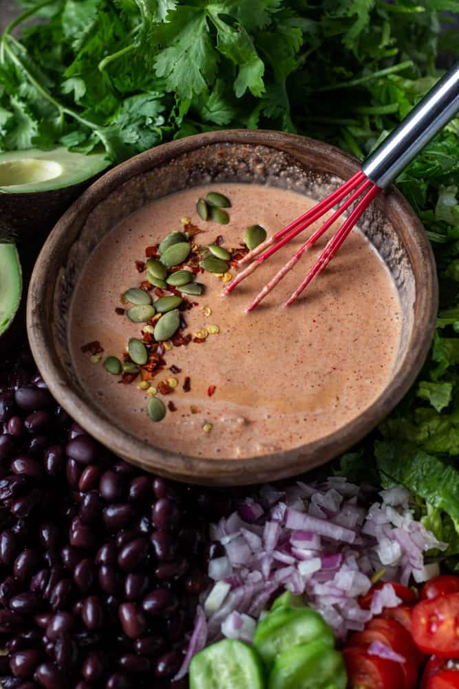 Bowl of tex-mex salad dressing in a bowl surrounded by salad ingredients.