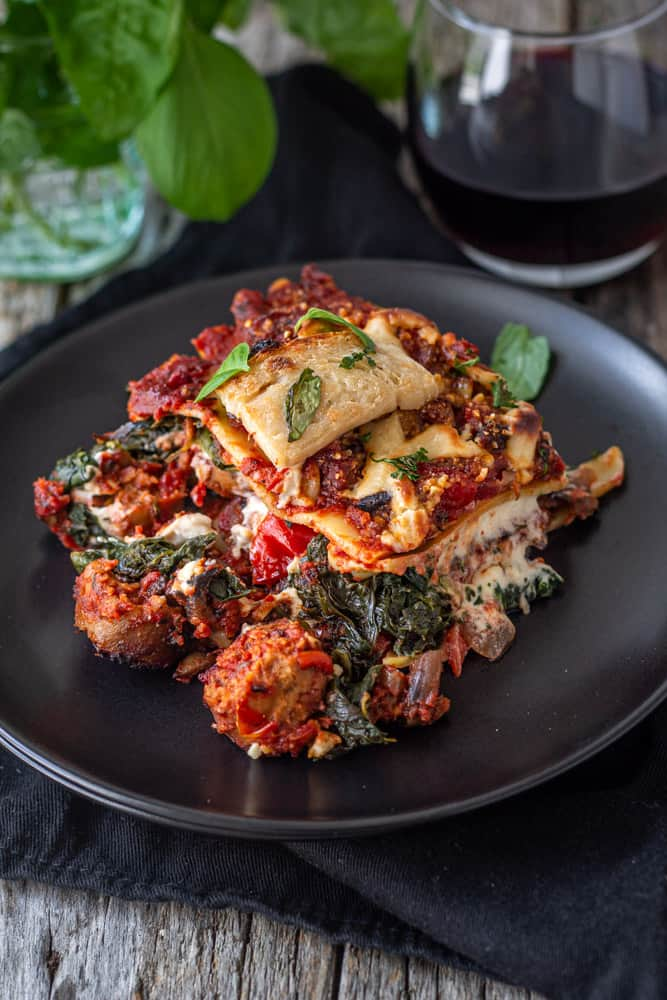 Vegan sausage lasagna on plate with a glass of wine.