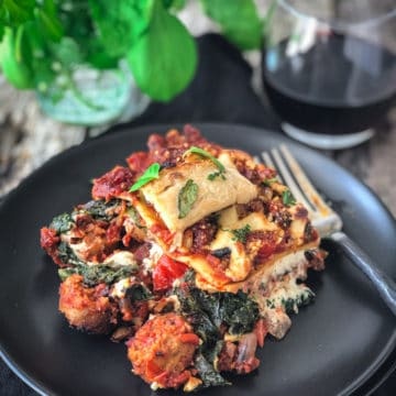 vegan sausage lasagna served on a plate with a fork and a glass of red wine