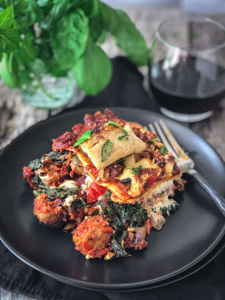 large piece of vegan sausage lasagna on a plate with a glass of wine