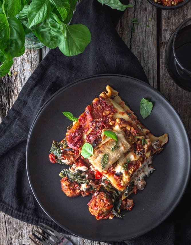 a large piece of vegan sausage lasagna on a plate with a fork and napkin
