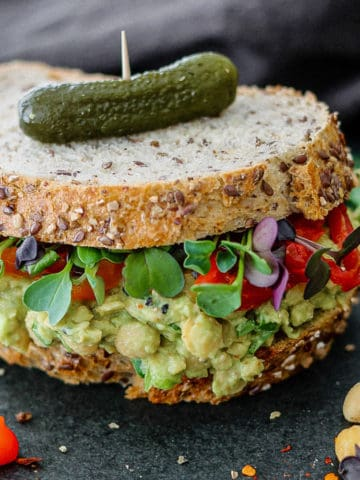Chickpea avocado sandwich on grainy bread with sprouts and pickle on top.