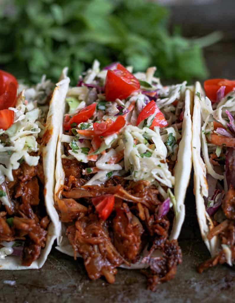 Close up of saucy jackfruit taco with creamy slaw on top and chunks of tomatoes.