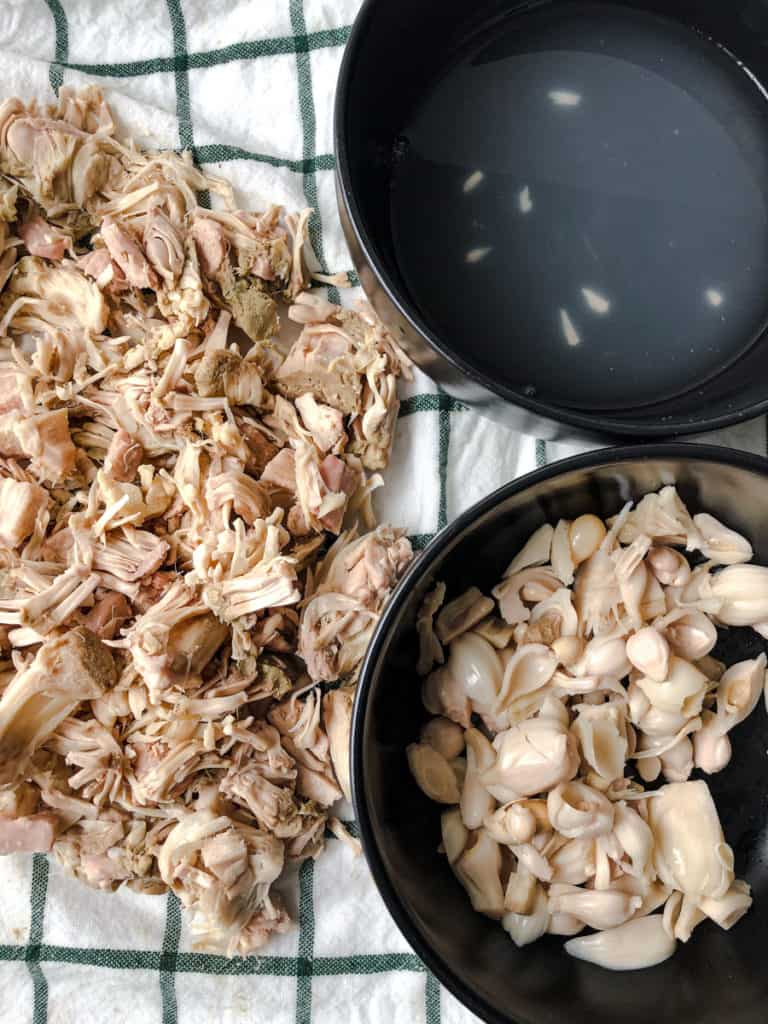 Pile of jackfruit plus two black bowls with water and jackfruit scraps.
