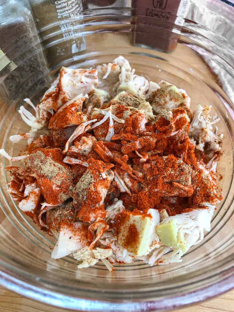 Jackfruit chunks being tossed with a dry spice rub in a glass bowl.