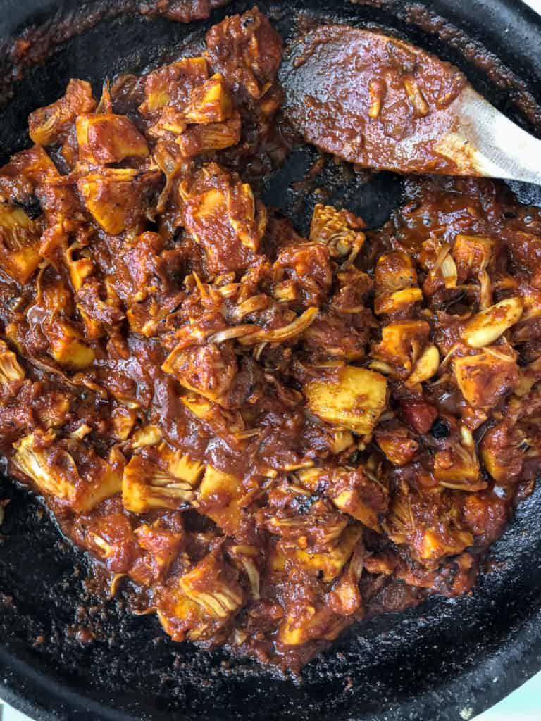 Jackfruit chunks being cooked in a spicy BBQ sauce in a cast-iron frying pan.
