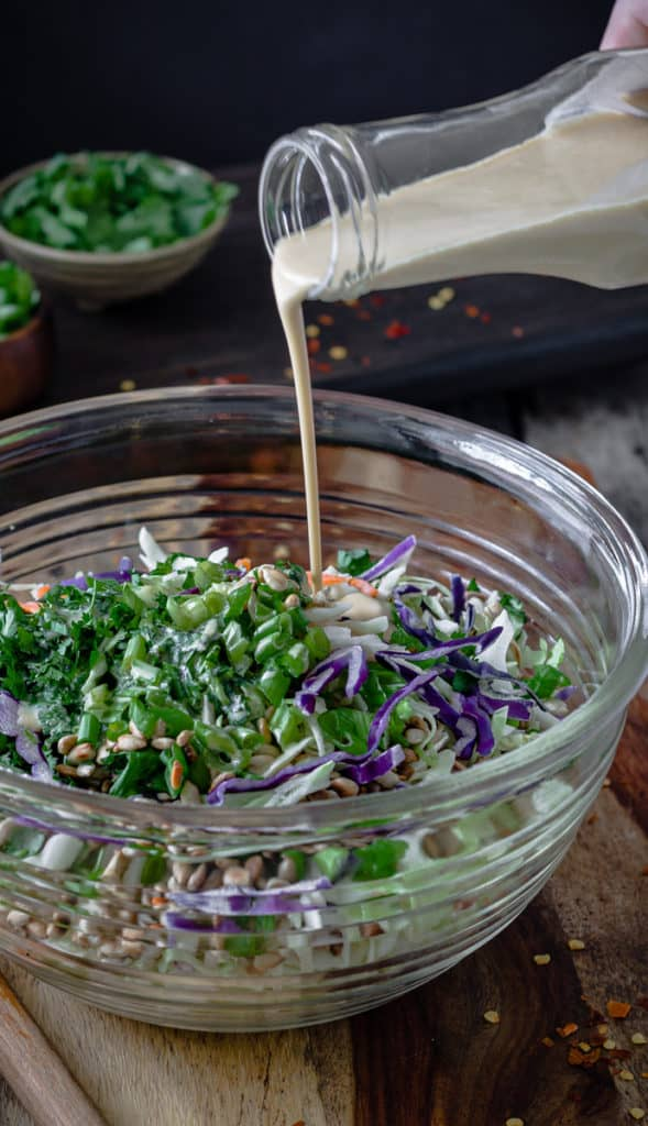 Dressing being pour into a colourful cabbage slaw.