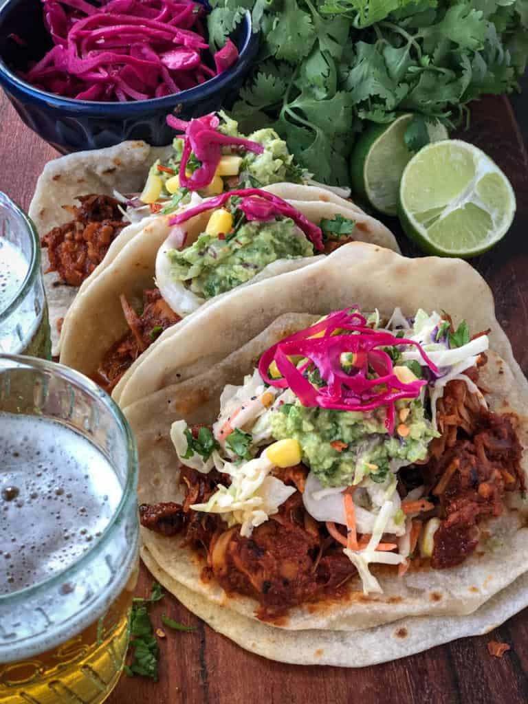 Vegan jackfruit tacos topped with tropical slaw, guacamole and pickled red onions.