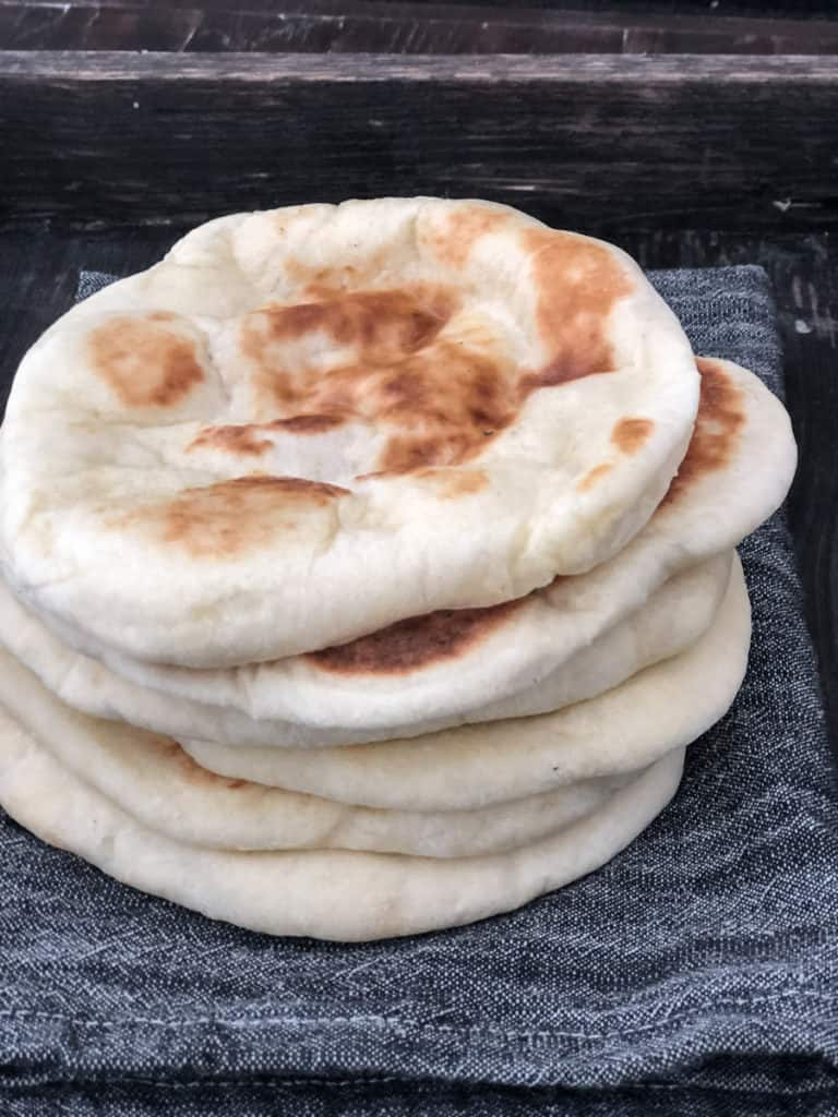 Stack of freshly made pita bread piled on a napkin.