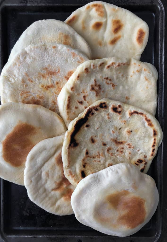 Baking tray filled with baked and fried pita bread.