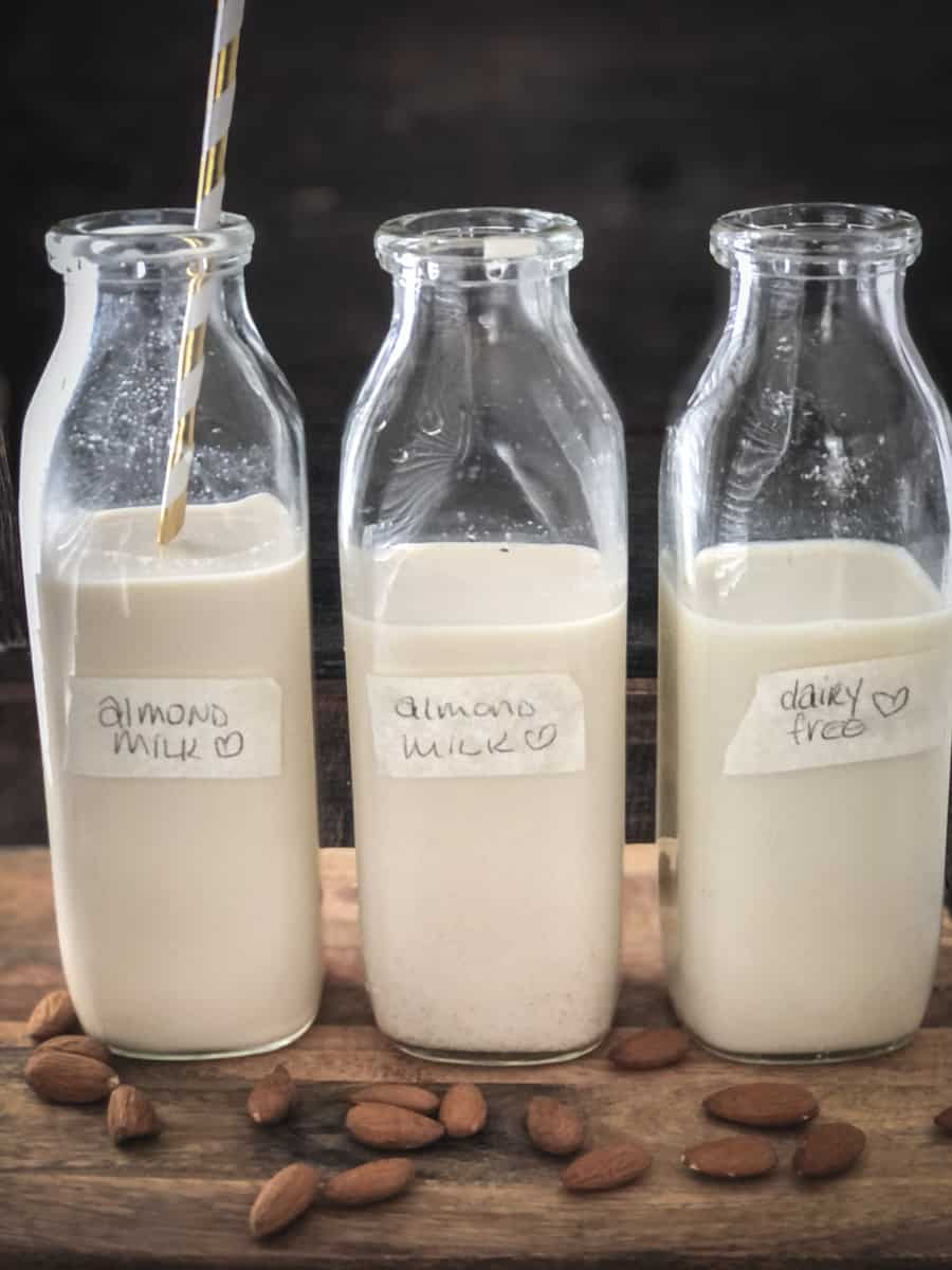 Three milk jugs of almond milk on a board with almonds scattered on it.