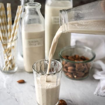 Fresh almond milk being poured into a glass on a tray with many jugs of milk and a bowl of almonds.
