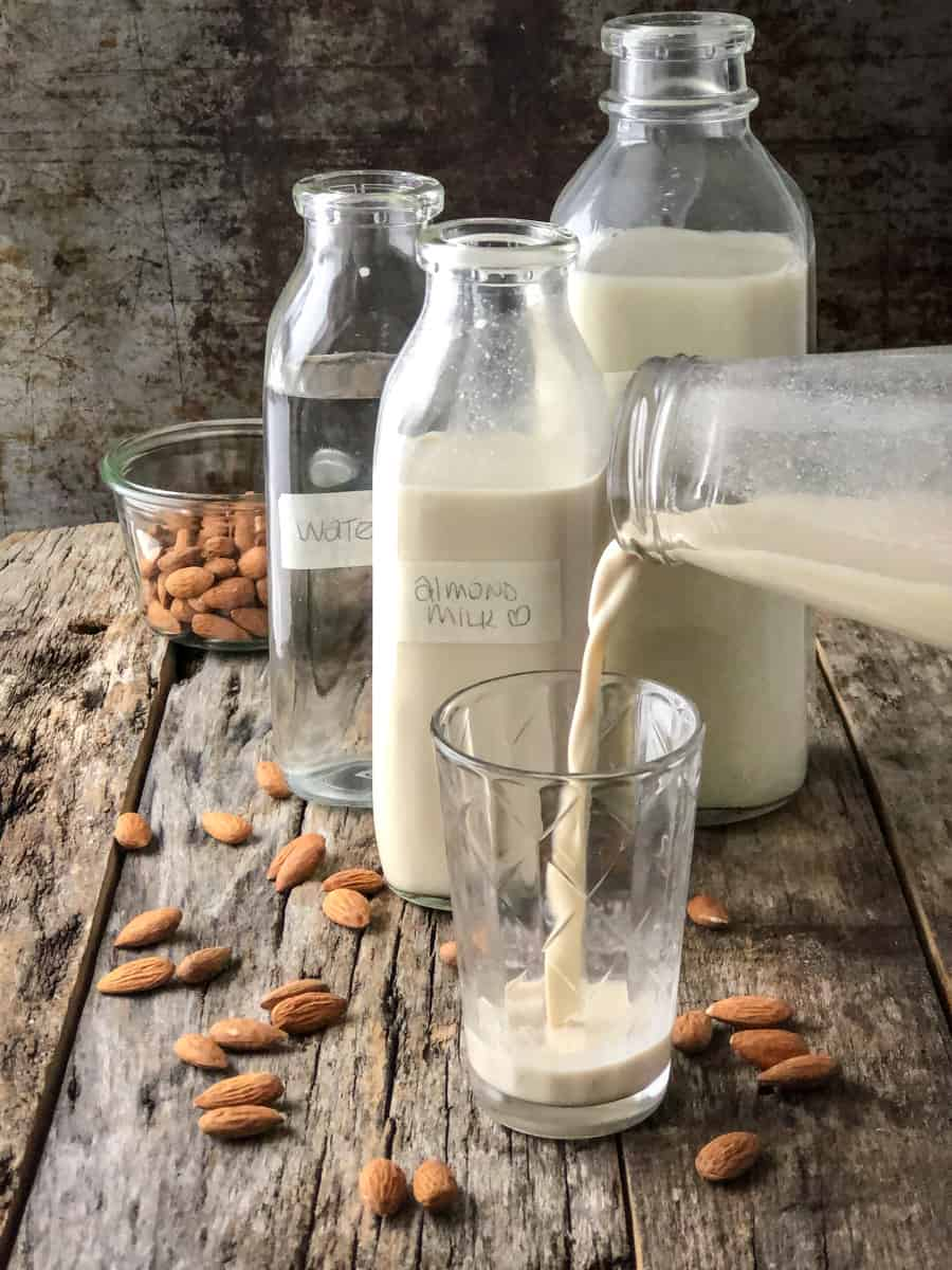 Almond mik being poured into a glass on a board with scattered almonds and several full milk jugs.