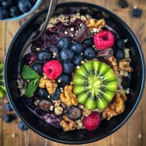 Bowl of porridge topped with berries and kiwi.