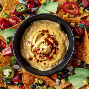 Bowlful of vegan queso cheese served in the middle of a plate of taco chips.