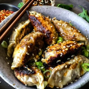 Bowlful of vegan potstickers sprinkled with sesame seeds and green onions.