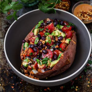 Baked sweet potato stuffed with taco seasoned tofu filling, black beans, tomatoes, and avocado served in a bowl.
