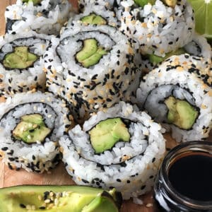 Sliced rolls of avocado sushi served on a plate with dipping sauce and avocado slices.