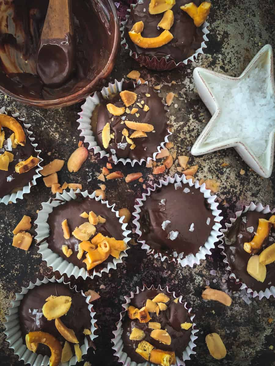 Mini peanut butter cups on a baking sheet topped with crushed pretzels and peanuts.
