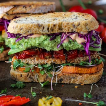Vegetable sandwich with guacamole, tomatoes, sweet potatoes and tofu on sourdough bread.