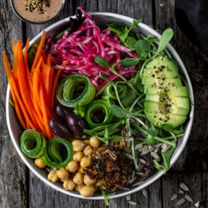 Fresh side salad with cucumber coils, carrots sticks, avocado slices, sprouts and chickpeas served in a big bowl.