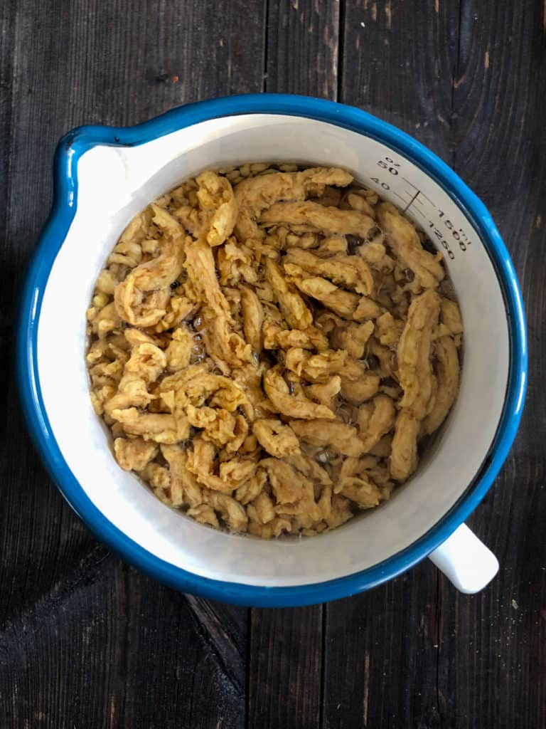 Soy curls covered in water soaking in a large measuring cup.