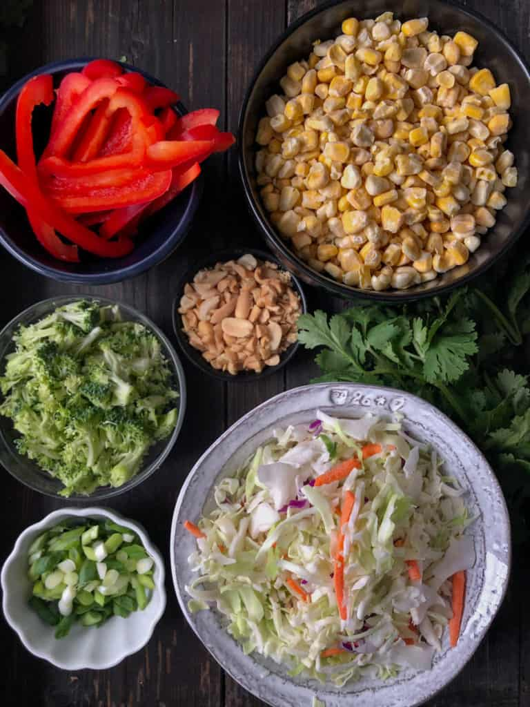Red peppers, corn and cabbage displayed in bowls on a baking sheet.