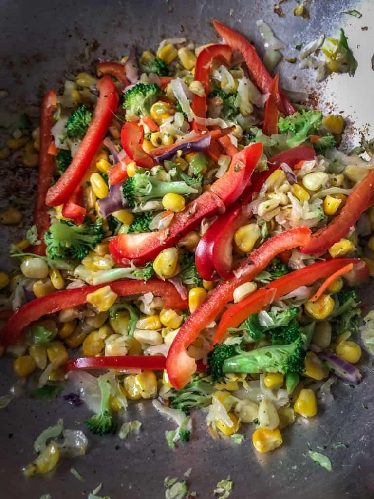 Vegetables in a wok being stir fried.
