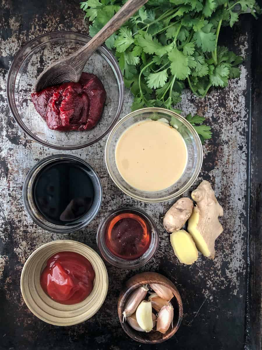 Spices and ingredients for ginger sauce measured out on baking tray.