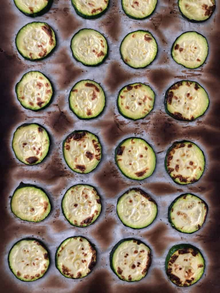 Baking sheet of grilled zucchini slices for vegan lasagna.