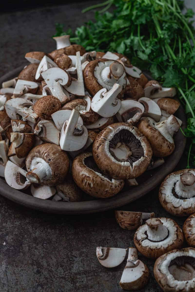 Chopped mushrooms in a dish with a few spilled onto the counter.