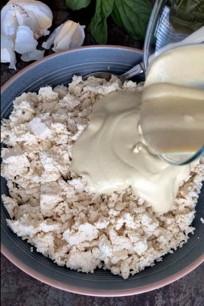 Cashew cream being poured into abowlful of crumbled tofu.