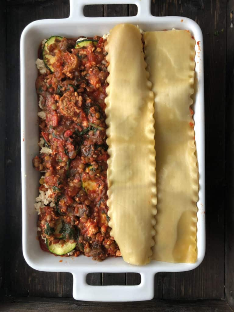 Overhead shot of noodles being layered on lasagne.