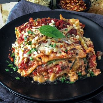 Slice of vegan lasagna on a plate topped with basil leaf.