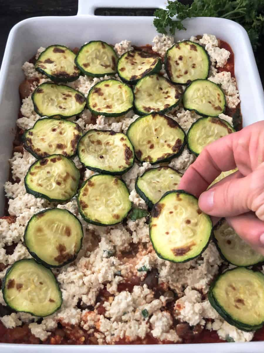 Zucchini slices being added to a layer of vegan lasagna.