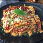 Slice of zucchini and mushroom vegan lasagna on a plate with basil leaf garnish.