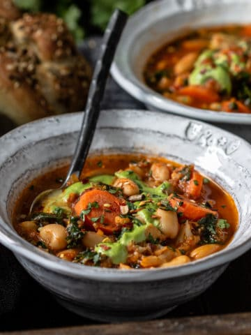 Bowl of vegetable bean soup with homemade buns.