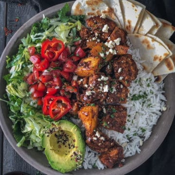 Overhead shot of buddha bowl with spicy tofu, tomatoes, avocado and rice.