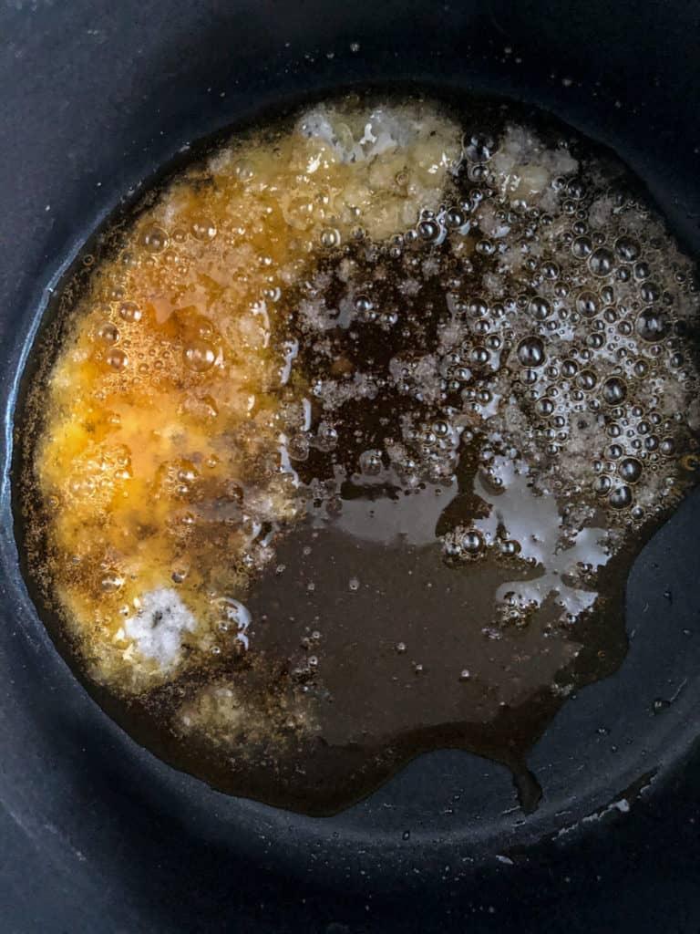 Sugar and water heating in a pan making caramel sauce.