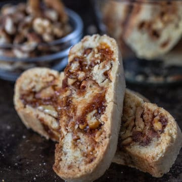 Two walnut praline biscotti on a plate with a bowl of cookies behind.
