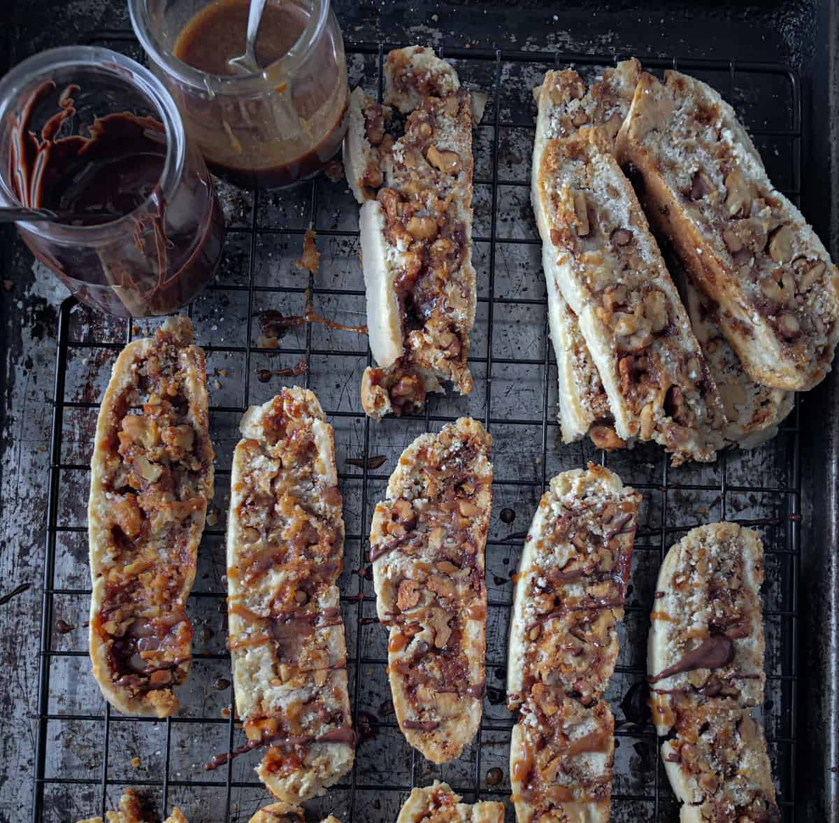 Baking sheet with biscotti and a pot of chocolate and caramel.