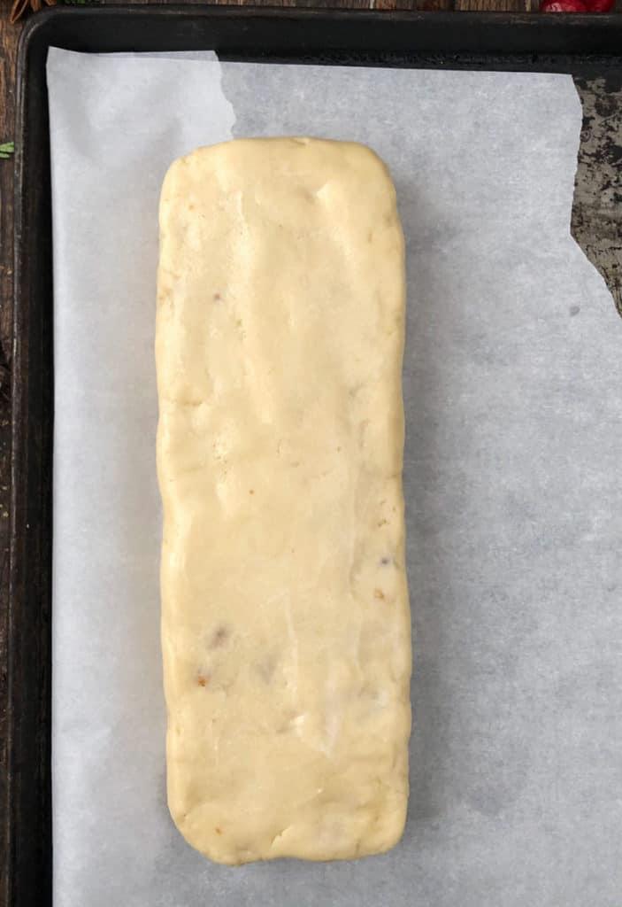 Overhead shot of walnut praline biscotti log being shaped.