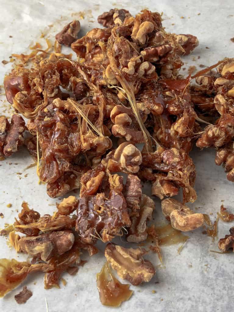 A pile of gooey walnut praline on a baking sheet.
