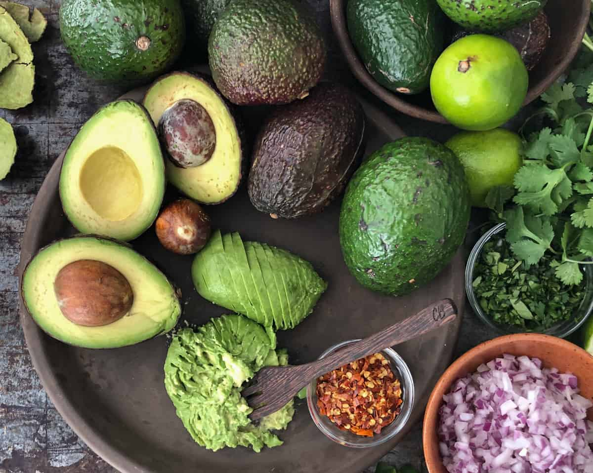Ingredients for making guacamole including avocados, limes, and onions on a baking sheet.