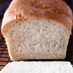 Loaf of fluffy white sandwich bread with a slice cut off.