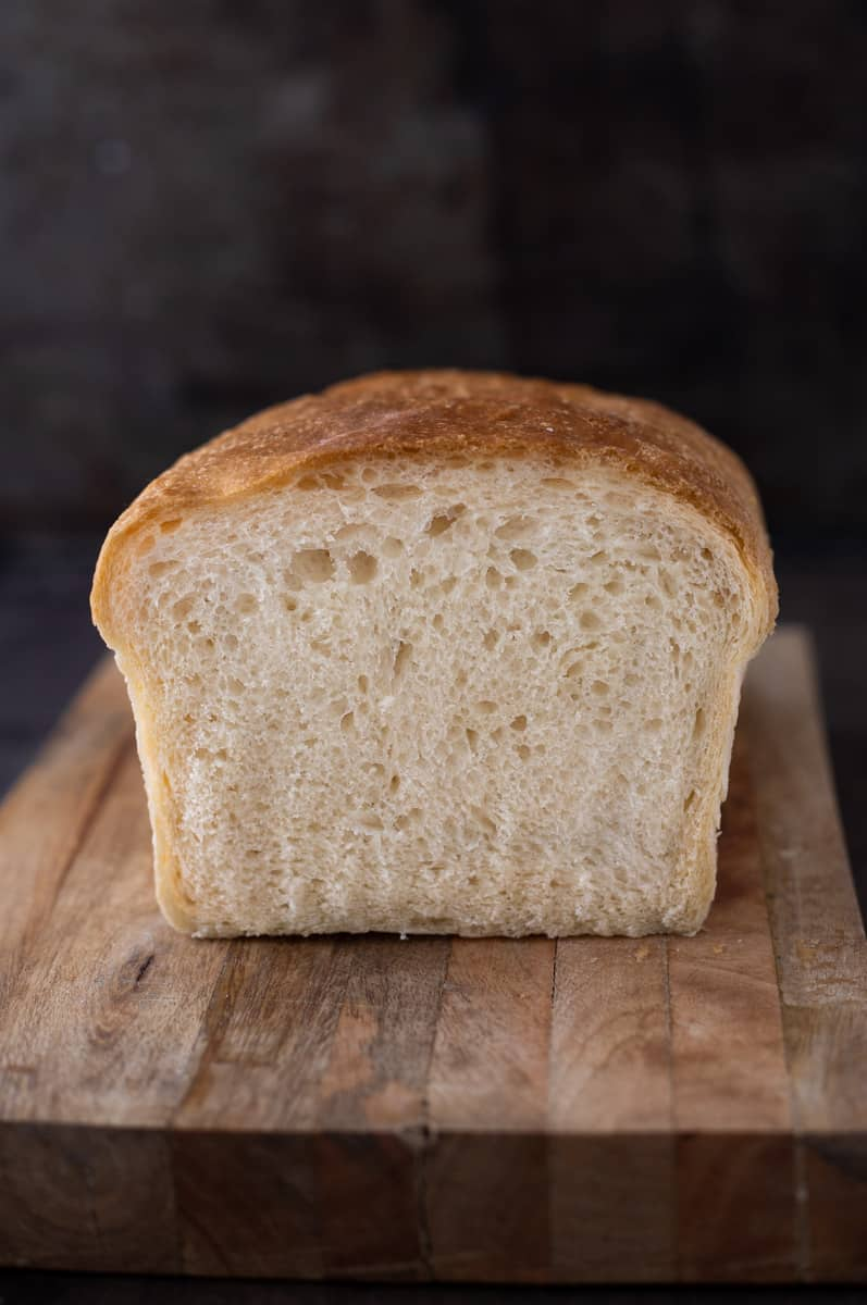 Loaf of white sandwich bread with one slice cut off.