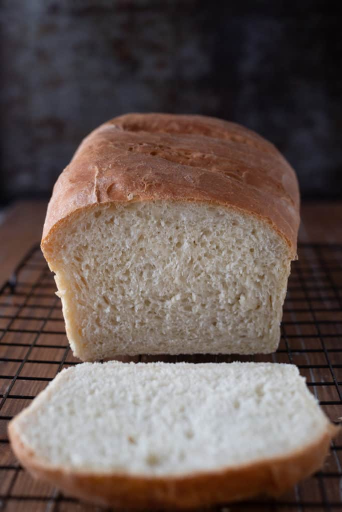 Freshly baked white loaf of white bread with one slice cut off.