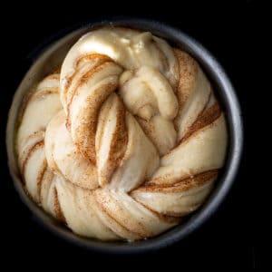 Cinnamon bun twist proofing in a tin.