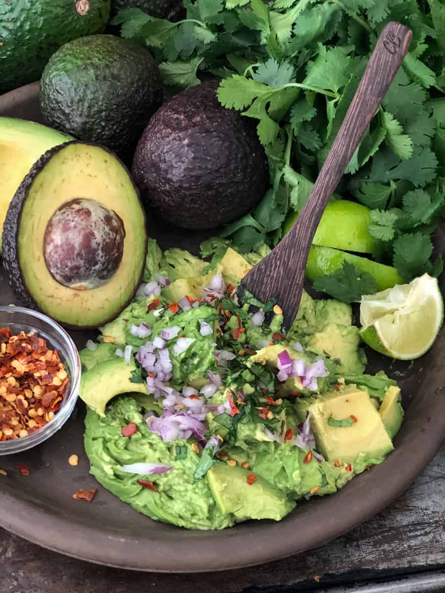 Guacamole being mashed on a large plate with whole and halved avocados piled in background.