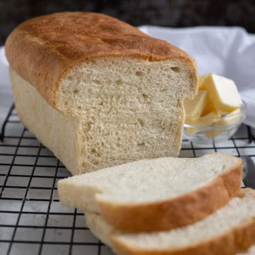 Loaf of white bread on cooling rack with 3 slices and a dish of butter.